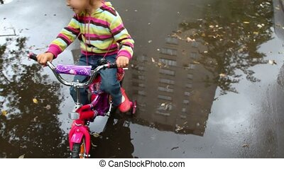 little girl sits on bicycle on wet asphalt with puddles,...