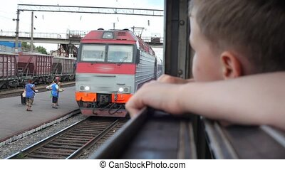 boy looks in train's window, another train going to camera