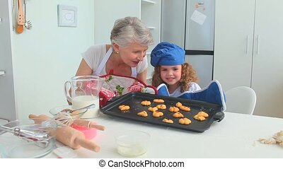 Girl and her grandmother after cooked looking at the camera