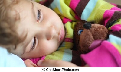 cute sleepy little girl with toy bear lying in bed and...