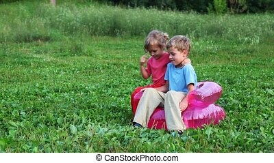 boy and girl sit in children's inflatable armchair on field...