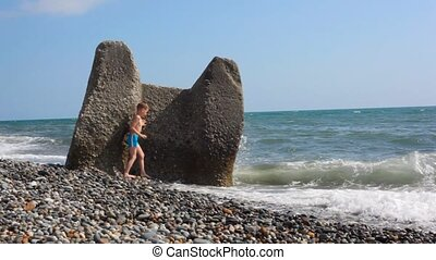 young boy hiding behind boulder in beach from sea surf