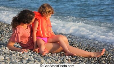 young mother with her little daughter lying in pebble beach near sea