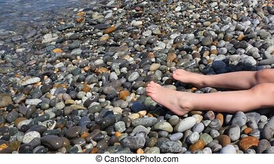 foots of little girl sitting in pebble beach near sea surf