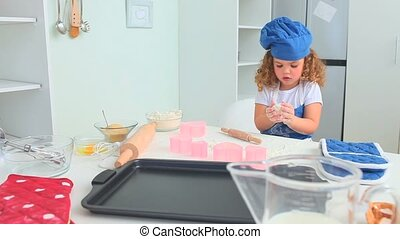 Little girl with an hat baking in the kitchen