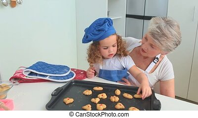 Cute curly-haired girl eating cookies with her grandmother...