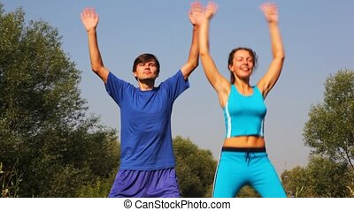 man and woman carries out exercises by hands in park...
