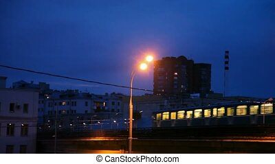 light rail train going in night residential area of city,...