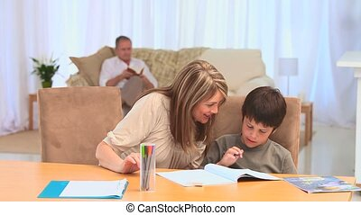 A boy doing his homeworks with his grandmother in the living...