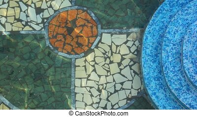 clear waving water in pool with mosaic floor, top view