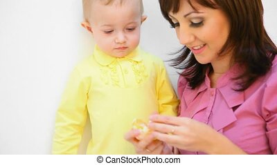 young mother feeding her little daughter with an orange against white background