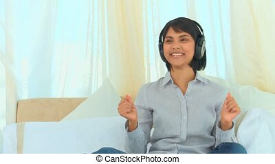 Casual chinese lady listening to music in her bedroom