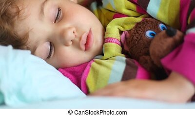 little girl sleeping with toy bear in compartment of railway...
