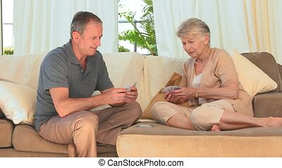 Lovely couple playing cards on the sofa