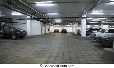 cars standing in underground car park, panning