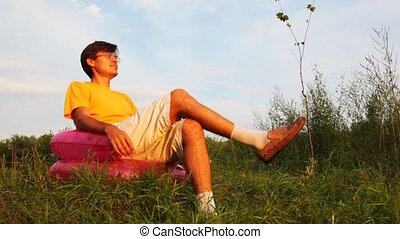man rest in childrens inflatable armchair in park Lapse time...