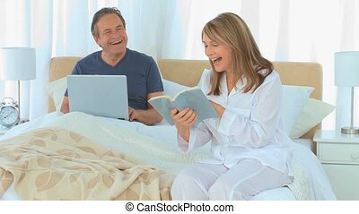 Mature couple with laptop and book in the bedroom