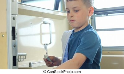 boy with towel brushing teeth in bathroom of carriage