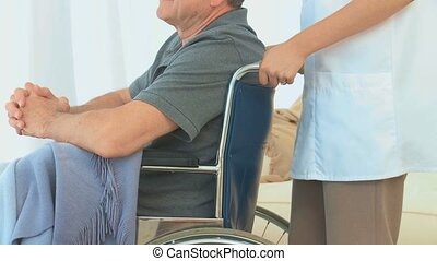 Man in a wheelchair listening to his asian nurse