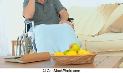 Man in a wheelchair laughing on the phone in his living room