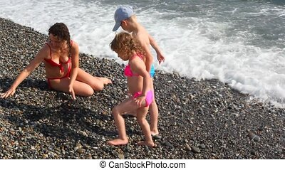mother with childs doing pile up of pebbles in surf sea beach