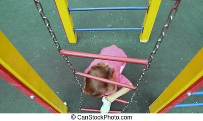 girl climb up on chain ladder also shakes on it on...