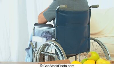 Man in a wheelchair looking through the window at home