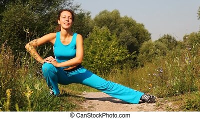 woman carries out exercises on path in park