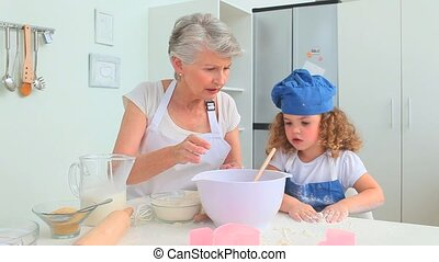 Cute curly haired girl baking with her grandmother