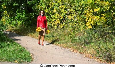 young woman with maple leaves in hands walking in autumn park