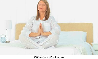 Mature woman doing yoga on her bed