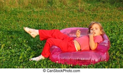 girl sit in children's inflatable armchair, holds finger in mouth and smile