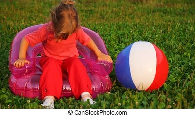 girl shake in children's inflatable armchair and take ball in hand
