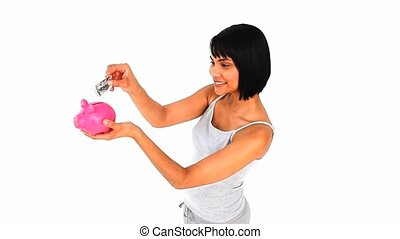 Cute asian woman saving up money in a piggy bank