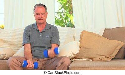 Elderly man using dumbbells in the living room