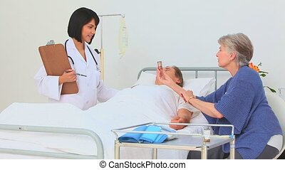 Nurse ginving explanations about pills to the wifes patient...