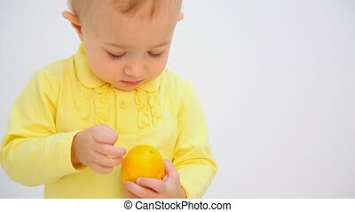 little girl peeling orange against white background