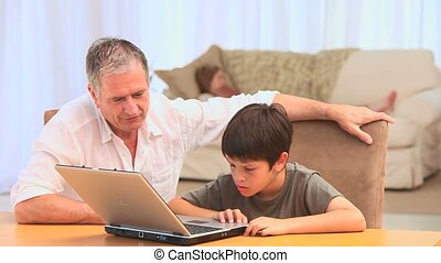 A grandfather and his grandson using a laptop in the living...