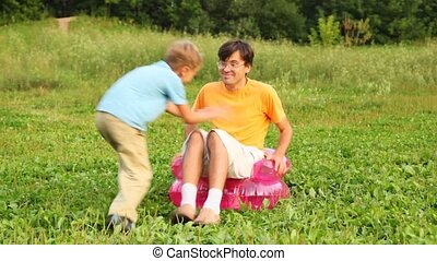 man, boy and girl sit in children's inflatable armchair on field in park and play the fool