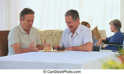 Men playing chess while their wives are speaking
