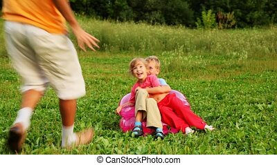 man, boy and girl play the fool sitting on an children's inflatable armchair on field in park