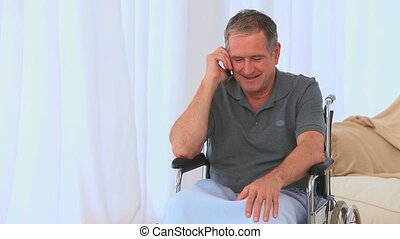 A male in a wheelchair having a phone call in his living...