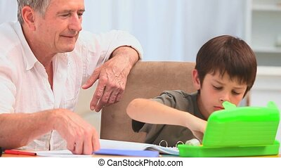 Cute little boy colouring with his grandfather on the table