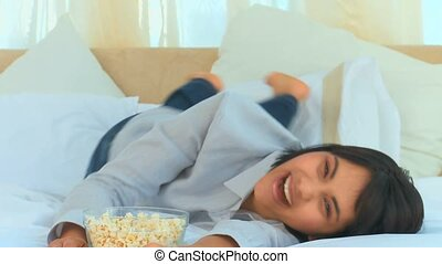Casual asian woman watching tv with popcorn in the bedroom