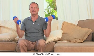 Middle aged man doing exercise of musculation with dumbbells...