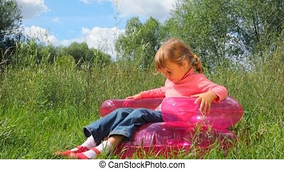 little cute girl rocking on inflatable chair outdoors in summer park