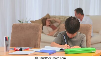 Little boy doing his homeworks after school in the living...