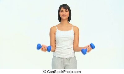 Cute asian woman using dumbbells isolated on a white...