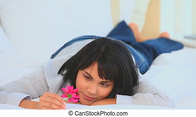 Cute asian woman holding a pink flower in her bedroom
