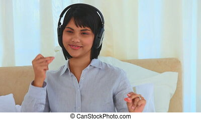 Asian woman listening to music with headphones in her...